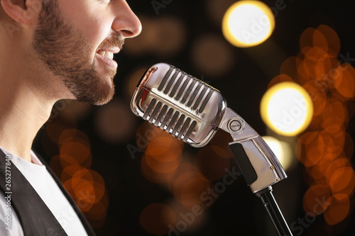 Handsome male singer with microphone on stage