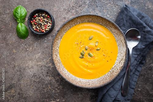 Fotografiet Vegetarian autumn pumpkin cream soup with seeds on dark background, top view