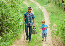 Boy And Father In Nature With Watering Can And Shovel. Dad Teaching Son Care Plants. Arbor Day. Planting Trees. Tree Planting Tradition. Little Helper In Garden. Planting Flowers. Growing Plants