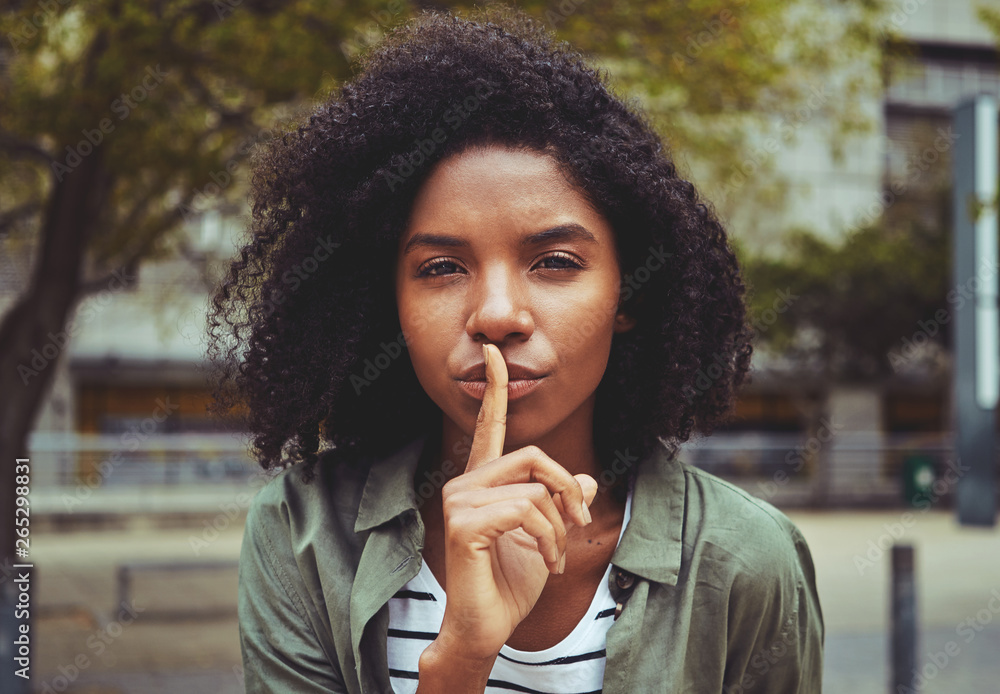 Fototapeta A young woman making silence gesture