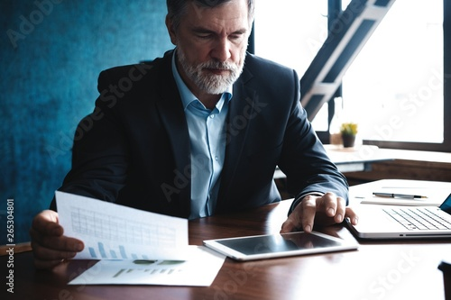 Garden Poster Serious mature financial advisor sitting at the table and checking financial report using digital tablet at office.