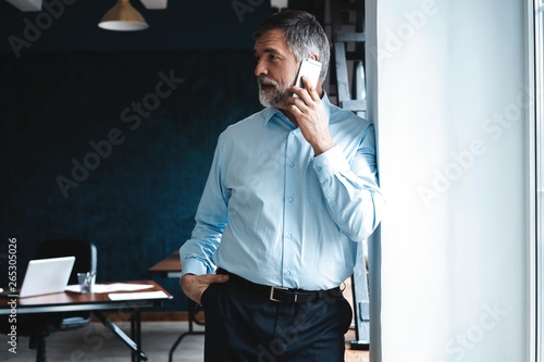 Mature businessman talking on a mobile phone standing by the window with view on city Fototapet