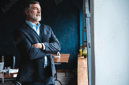 Fotografia  Mature businessman in a corporate suit standing in office and looking away through large windows optimistically