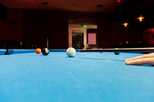 A Billiard Carbon Cue. Table With Billiard Cue And Balls. White And Black Ball Number 8