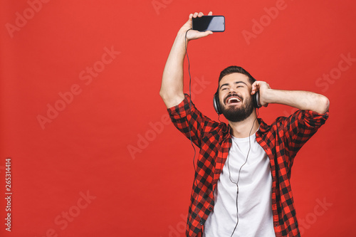 Image of unshaved man 30s singing while listening to music with earphones and mobile phone isolated over red background. - 265314414