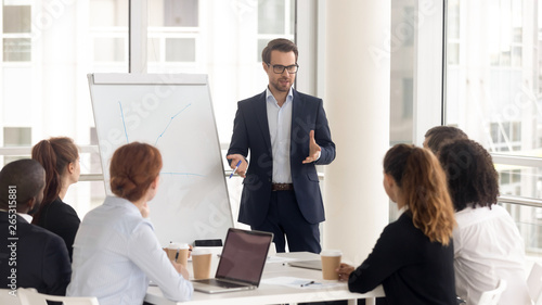 Male business coach speaker in suit give flipchart presentation