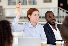 Businesswoman Raising Hand Ask Question At Diverse Group Corporate Training