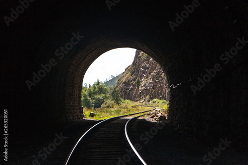 Fotografering  light with a landscape at the end of a stone railway tunnel with beautifully lit
