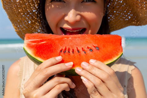 Fotografia Charming beautiful young woman eating watermelon to cool down and quench her thirst in summer season at beach