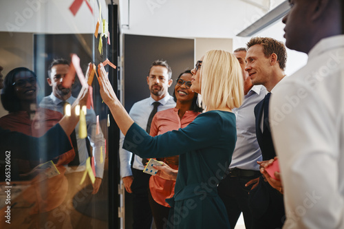 Fototapety, obrazy: Young businesswoman and her team brainstorming with sticky notes