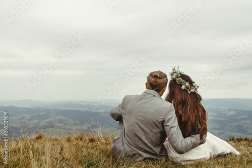 Photo  gorgeous bride and stylish groom sitting on top,  boho wedding couple, luxury ceremony at mountains with amazing view, space for text