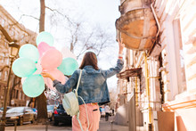 Portrait From Back Of Girl With Trendy Bag Walking Down The Old Street Carrying Bunch Of Colorful Balloons. Stylish Young Woman Wearing Denim Jacket And Pink Pants Going To Party With Peace Sign