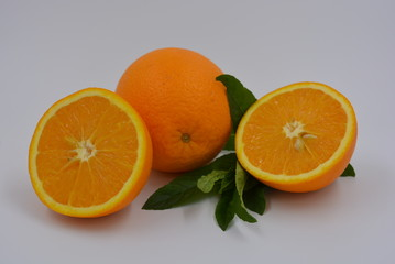 Bright two orange halves of cut ripe and large juicy orange and a branch of fresh mint. Healthy food and fruit, health and sport.