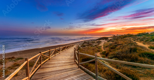 View of amazing bright sundown sky over waving sea and wooden path in countryside in Cabopino, Artola dunes. Marbella, Spain