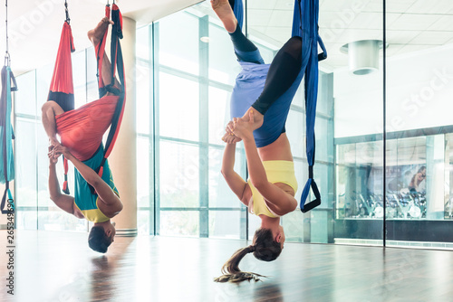 Fotografía  Fit young woman practicing aerial yoga in a modern fitness club