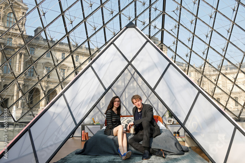 Airbnb contest winners pose on a bed under the glass Pyramid