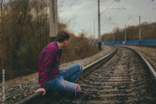 Fototapety, obrazy: Trendy young man sitting on rails. Pensive male in jeans and red shirt on railway in evening of cloudy day