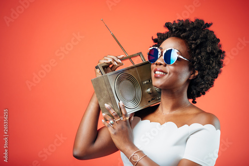Black girl with sunglasses dancing to a hip song playing from the boombox - 265356255