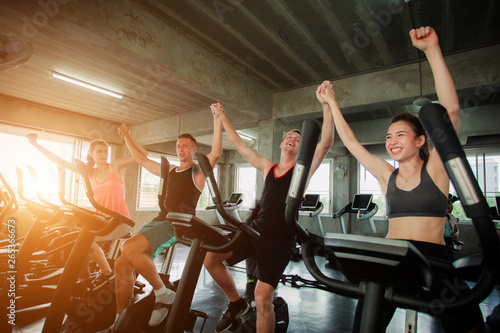 Group portrait of happy people working out at spinning class in gym doing sport Fototapeta