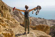A Young Woman Stands With Arms Outstretched At The View Of The Dead Sea While Hiking In Ein Gedi, Dead Sea District; South District, Israel