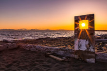 A Sunburst Shines Bright Through The Window Of A Weathered, Wooden Door Propped Up On Iona Beach; Richmond, British Columbia, Canada
