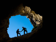 A Young Couple Climbing In The Mouth Of A Cave, Holding Hands For Support; Fernie, British Columbia, Canada