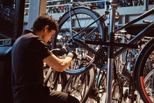 Young Attractive Mechanic Is Fixing Customer's Bicycle At His Own Workshop.