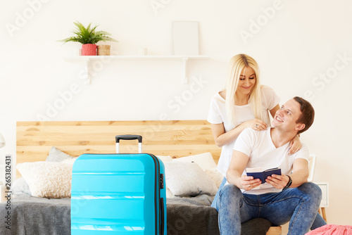 fototapeta na szkło Smiling couple of tourists with passports and tickets in hotel room keep a suitcase with luggage. Waiting for a flight from the airport. The girl hugs the guy, they are going on a honeymoon trip