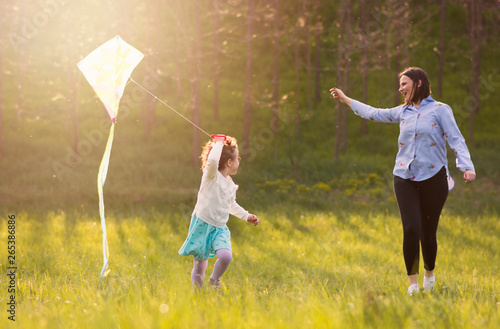 sweet little girl running with kite at the sunny meadow,mothers watchin Tablou Canvas