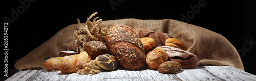 Assortment of baked bread and bread rolls on rustic white bakery table background