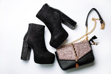 Black Suede Ankle Boots On A Platform And Thick Heels With Sparkles And A Black Bag With Sparkles On The Flap On A White Background