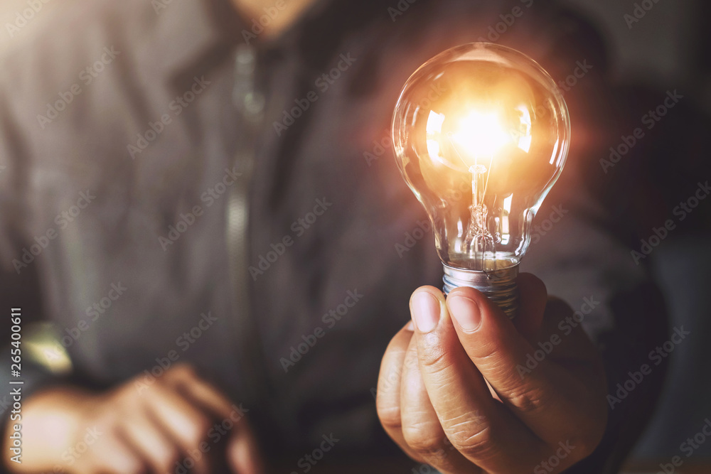 Fototapety, obrazy: hand holding light bulb. idea concept with innovation and inspiration