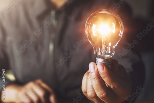 Obraz hand holding light bulb. idea concept with innovation and inspiration - fototapety do salonu