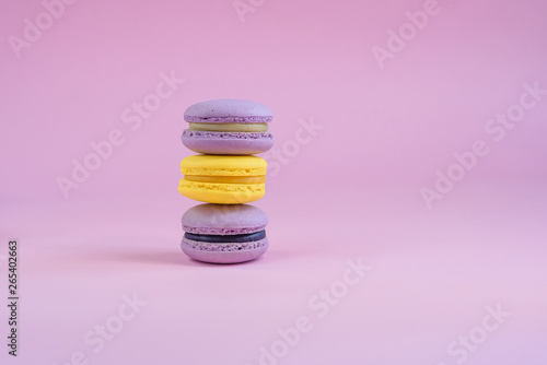 Fotobehang Macarons Tasty violet and yellow french macaron cakes on yellow background.
