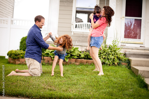 Foto  Happy Family Playing in Yard in Front of Their Home