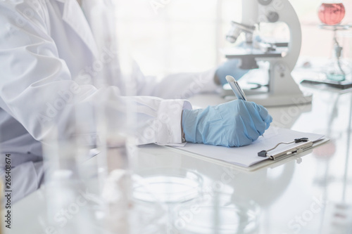 Fotografia  A scientist hands writing on a clipboard in laboratory with test tube microscope and solutions