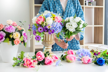 young women business owner florist making or Arranging Artificial flowers vest in her shop, craft and hand made concept