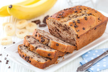 Delicious Homemade Banana Bread With Chocolate Chips Sliced On A White Serving Tray With Ingredients At The Background