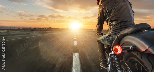 Motorcycle driver riding alone on asphalt motorway