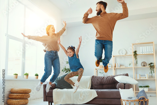 Papiers peints Individuel happy family mother father and child daughter dancing at home
