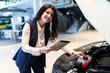 Beautiful sale-manger inspect new car with help of tablet in dealership center