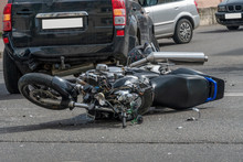 Broken Motorcycle Closeup Beside The Car. An Accident On The Road In The City On A Sunny Day Involving A Motorcycle And A Car.