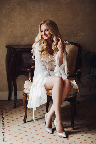 Portrait of beautiful and sensuality blondie bride sitting on chair in luxury interior, dreaming about husband, looking down Wallpaper Mural
