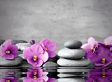 Fototapeta Kwiaty - Pink flower and stone zen spa on grey background