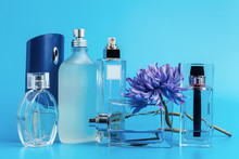 Perfume Bottles With Flowers On A Light Blue Background