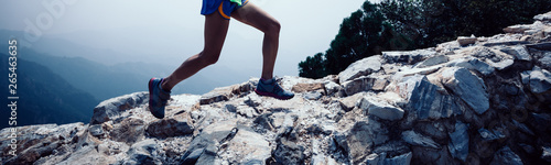 Fotografiet  Fitness woman trail runner running at great wall on the top of mountain