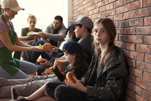 Teenage Girl With Other Poor People Receiving Food From Volunteers Indoors