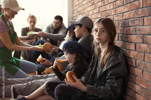 Teenage girl with other poor people receiving food from volunteers indoors Canvas