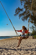 Vacation concept. Young woman swing on a beach swing. Happy traveller women on the Phu Quoc beach