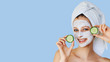 canvas print picture Beautiful young woman with facial mask on her face holding slices of cucumber. Skin care and treatment, spa, natural beauty and cosmetology concept.